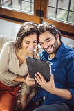 Young Couple Sitting On Sofa Using Digital Tablet Royalty Free Stock Photos