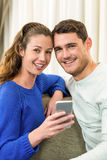 Young couple sitting on sofa and using mobile phone Stock Photography