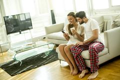 Young couple sitting on a sofa after waking up. And looking at the phone, women drinking coffee Royalty Free Stock Image