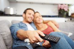 Young Couple Sitting On Sofa Watching Television Stock Photo