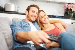 Young Couple Sitting On Sofa Watching Television Stock Image