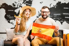 Young couple dreaming about a trip to Spain. Young couple sitting with spanish flag at the travel agency office on the world map background prepairing for a trip Stock Photo