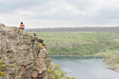 Young couple sitting on a steep rocky cliff Stock Photography