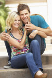 Young Couple Sitting On Steps Of Building Royalty Free Stock Image