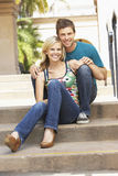 Young Couple Sitting On Steps Of Building Royalty Free Stock Photos