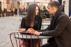 Young couple sitting at the street cafe. Romantic date stock photography