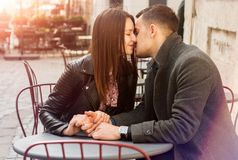 Young couple sitting at the street cafe in the sun flare. Romantic date royalty free stock photo