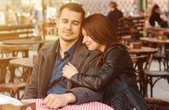 Young couple sitting at the street cafe in the sun flare. Romantic date royalty free stock image