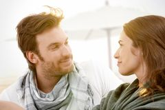 Young couple sitting on summer beach smiling. Young couple sitting on summer beach with blanket enjoying sunset, looking at each other, smiling Royalty Free Stock Photos
