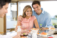 Young couple sitting at sushi bar, smiling, portrait Royalty Free Stock Photo