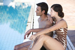 A young couple sitting by a swimming pool Stock Image