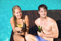 Young couple sitting at the swimming pool Stock Image