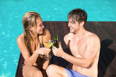 Young couple sitting at the swimming pool Stock Images