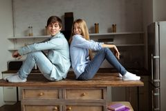 Young couple sitting on the table back to back royalty free stock images