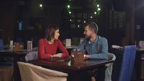 Young couple sitting at a table in a cafe and talking stock footage