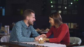 Young couple sitting at a table in a cafe and talking stock video