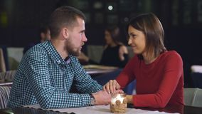 Young couple sitting at a table in a cafe and talking. First date, beautiful brunette woman in red dress stock video