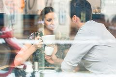 Young couple sitting at a table while drinking coffee and cappuc royalty free stock photos