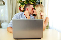 Young couple sitting at the table and kissing. At home Royalty Free Stock Photos
