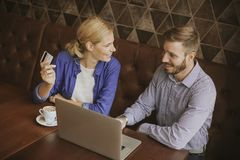 Young couple with laptop in restaurant. Young couple sitting by the table with laptop in restaurant and doing online shopping royalty free stock photo