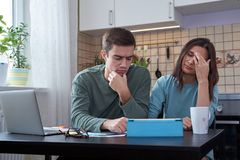 Young couple sitting at the table in kitchen are engaged in planning and calculating finances. Tired face, and negative emotions stock images