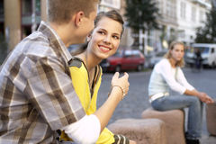 A young couple sitting, a teenage girl sitting alone. Royalty Free Stock Image