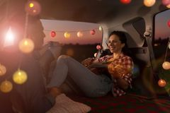Young couple sitting in their car trunk and watching the sunset royalty free stock photos