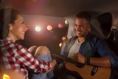 Young couple sitting in their car trunk and watching the sunset stock photography