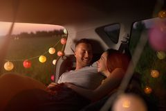 Young couple sitting in their car trunk and watching the sunset stock image