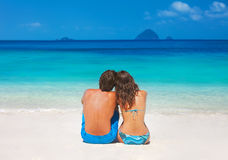 Young couple sitting together on the beach Stock Photo