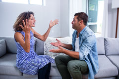 Young couple sitting together and discussing after a fight stock photography