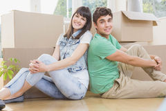Young couple sitting together on the floor and smiling Royalty Free Stock Photography