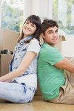 Young couple sitting together on the floor and smiling. In their new house Royalty Free Stock Photo