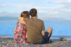 Young couple sitting together on a rocky beach and looking at th Stock Photo