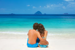 Young couple sitting together on a sandy tropical beach Stock Image