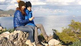 Young couple sitting on the top of the rock stock video footage