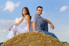Young couple sitting on top of a straw bale Stock Images
