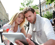 Young couple sitting in town using tablet Stock Image