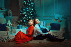 Young couple sitting under the Christmas tree. Stock Photo