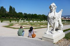 Young couple sitting under a sculpture in Schonbrunn Palace garden Stock Photos