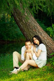 Young couple sitting under tree Stock Image
