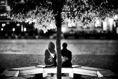 Young couple sitting under the tree Royalty Free Stock Image
