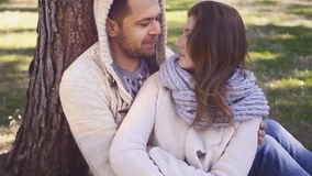 Young couple sitting under the tree. Young couple sitting toghether under the tree in the park in spring, slow motion stock footage