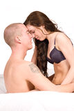 Young couple sitting up in bed fondling Stock Image