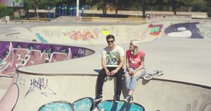 Young couple sitting on a wall at a skate park stock video footage