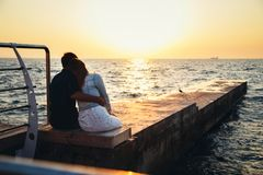 Young couple sitting and watching the sunrise at the beach, back view, seashore summer beach at yellow blue morning horizon sea royalty free stock image