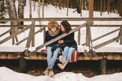 Young couple sitting on wooden bridge in winter forest Stock Images