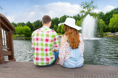 Young couple sitting on the wooden deck and feeding ducks in a p Royalty Free Stock Images