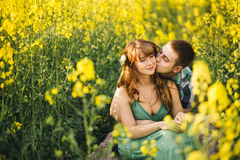 Young couple sitting among yellow flowers in meadow embrscing, man kissing his pretty wife. Girlfriend wearing green dress, husban Stock Photo