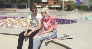 Young couple of skateboarders sitting chatting stock footage